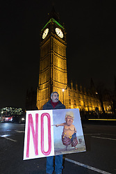 Whitehall, London, January 30th 2017. Tens of thousands protest outside the gates of Downing Street against an invitation by HM the Queen to US President Donald Trump for a State Visit, a date for which has still to be set. The protests come following Trump's executive Order for the temporary ban on Muslims and refugees from seven countries from entering the United States. A petition  against the visit started following the ban has gathered well over a million signatures.PICTURED: Satirical political artist Kaya Mar displays his latest painting.