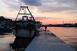 Uomo cammina al tramonto sulla banchina del porto di Taranto.
