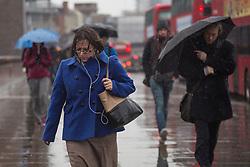 © licensed to London News Pictures. London, UK 14/12/2012. People walking under rain on London Bridge on 14/12/12. Photo credit: Tolga Akmen/LNP
