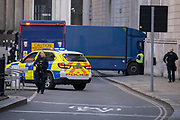 With nearby streets blocked off, a convoy of heavy high-security vehicles carrying high-value assets is accompanied by an armed escort of police officers into the Lothbury entrance of the Bank of England, on 1st March 2021, in London, England.