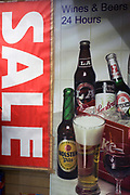 A sale sign and poster for alcoholic drinks like bottles of beer and glass of wine in a London off-license window. We see bottles of Holsten, Becks and something called LA plus the lager beer in a glass and the glass of red wine all shown as pack shots in a studio setting. At the top we read that wines and beers are available 24/7 in this convenience shop at the southern end of Westminster Bridge in the heart of the inner city.