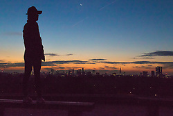 Primrose Hill, London, October 28th 2016. XA woman surveys the city skyline as dawn breaks over London.
