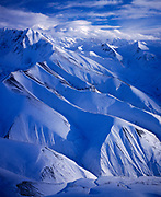 Aerial view in winter of Pyramid Peak with lenticular clouds over the University Range of the Saint Elias Mountains beyond, Wrangell-St. Elias National Park and Preserve, Alaska.