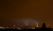 Lightning and thunder storm over the Eiffel Tower in Paris. Dark sky and several lightnings and the Eiffel tower lit up uplit