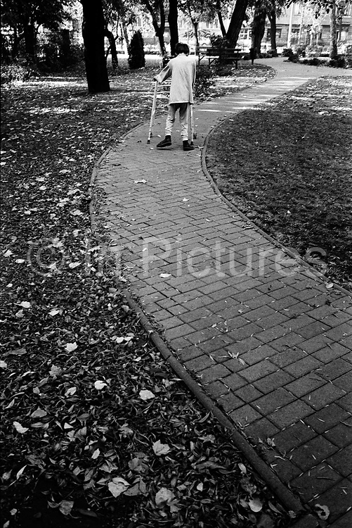 A child with cerebal palsy walks around the garden during his morning exercise at the Peto Institute.