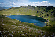 Red Tarn lake high up on the eastern flank of Helvellyn Mountain, English Lake District, Cumbria, United Kingdom on the 2nd of August 2021. Red Tarn is a glacial lake formed with the glacier that carved our the eastern side of the mountain melted. It is the habitat of the rare and endangered Schelly fish.