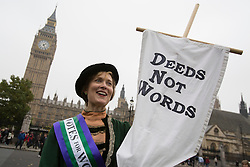 "© licensed to London News Pictures. London, UK 24/10/2012. A member of UK Feminista posing outside the Houses of the Parliament with a placard reading ""Deeds not Words"" as UK Feminista members meet for a mass lobby with Dr Helen Pankhurst, granddaughter of Emmeline Pankhurst and calling on MPs to stop erosion of women's rights and drive forward progress on women's equality. Photo credit: Tolga Akmen/LNP"