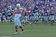 Kansas State's Maurice Marc (24) jumps into the air as the Wildcats storm the field after beating Oklahoma State, as Cowboy Brady Bond (60) walks off the field at Bill Snyder Family Stadium in Manhattan, Kansas, October 7, 2006.  The Wildcats beat the Cowboys 31-27.<br />
