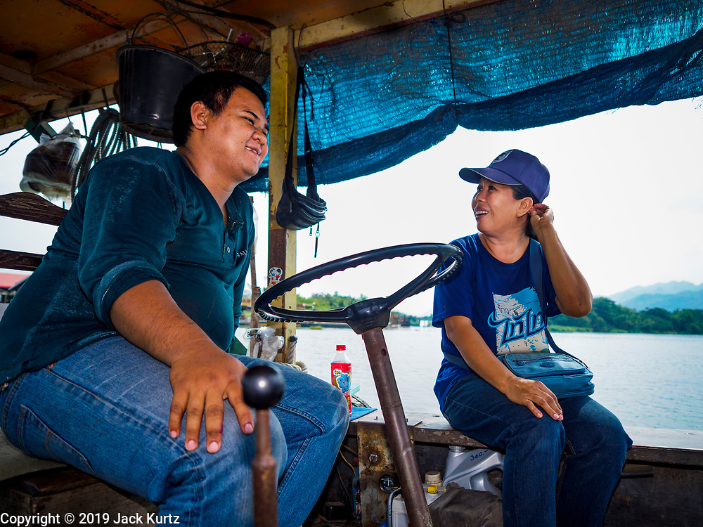 """09 JANUARY 2019 - KANCHANABURI, THAILAND: BOM, the operator of a small ferry on the River Kwai near Kanchanaburi, chats with one of his passengers. The ferry goes across the River Kwai downriver from downtown Kanchanaburi, the site of the famous """"Bridge on the River Kwai."""" Small ferries like this, once common on Thai river crossings, are disappearing because Thailand has dramatically improved its infrastructure since this ferry started operating about 50 years ago. The ferry operator said his grandfather started the ferry, with a small raft he would pole across the river, in the late 1960s. Now his family has a metal boat with an inboard engine. There are large vehicle bridges across the river about 5 miles north and south of this ferry crossing, but for people in rural communities on the west side of the river the ferry is still the most convenient way to cross the river.      PHOTO BY JACK KURTZ"""