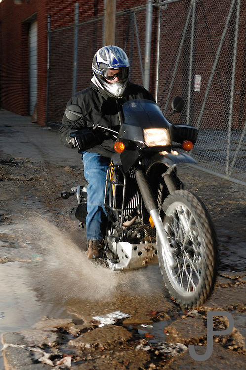 Dual sport motorcycle rider on Kawasaki KLR 650 splashing through water puddle in alleyway in downtown Oklahoma City.