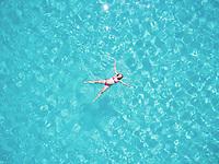 Beautiful woman swimming in transparent sea
