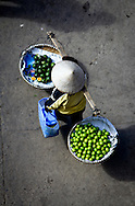Top view of a street vendor wearing a conical hat carrying a yoke with fruit as she walks through Dalat's market, Lam Dong Province, Vietnam, Southeast Asia