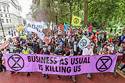 """Protestors dressed as a clown circus outside the HM Treasury building, march towards Trafalgar Square during an Extinction Rebellion protest called """"Corruption Carnival"""" in Westminster, central London on Wednesday, Sept 3, 2020. The environmental campaign group has planned events to be held at several landmarks in the capital. Extinction Rebellion plans to hold 10 days of demonstrations across central London as part of its ongoing campaign to highlight climate change. Environmental nonviolent activists group Extinction Rebellion enters its 3rd day of continuous ten days to disrupt political institutions throughout peaceful actions swarming central London into a standoff, demanding that the central government obeys and delivers Climate and Ecological Emergency Bill and prepare for crisis with a National Citizens' Assembly. (VXP Photo/ Vudi Xhymshiti)"""