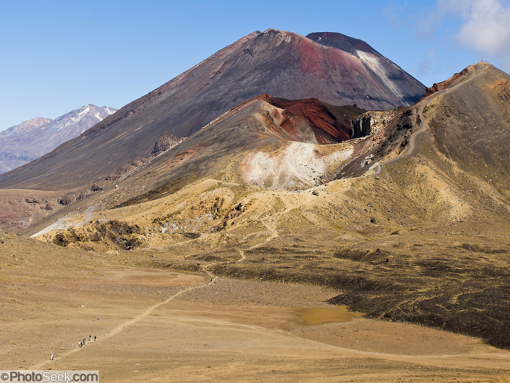 """Trampers hike the 10-mile Tongariro Crossing beneath Mount Ngauruhoe in Tongariro National Park, North Island, New Zealand. The volcanoes in this image are: Mount Ruapehu (with snow at far left, 2797 meters or 9177 feet, last erupted in 2006), Mount Ngauruhoe (upper middle, 2291 meters or 7516 feet elevation, last erupted in 1975), and Red Crater (foreground right, 1886 meters, last erupted 1926). Geologically speaking, both Mount Ngauruhoe and Red Crater are vents of Mount Tongariro. In 1990 and 1993, UNESCO honored Tongariro National Park as a World Heritage Area and Cultural Landscape. Tongariro National Park served as a location for fictional Mordor and Mount Doom in the """"Lord of the Rings"""" Motion Pictures. Published in """"Light Travel: Photography on the Go"""" by Tom Dempsey 2009, 2010."""