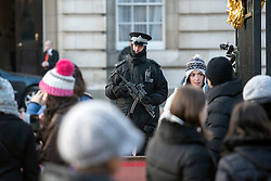 © Licensed to London News Pictures. 29/01/2015. London, UK. Scotland Yard is set to train hundreds more officers as a reserve firearms unit to deal with a possible terrorist gun attack on London. Met Commissioner Sir Bernard Hogan-Howe said the force was reviewing the number of armed officers in the wake of the Paris outrages. FILE PICTURE (22/01/15) OF Armed Police officers in the grounds of Buckingham Palace during The Changing of the Guard.  Armed police officers in and around central London today 22 January 2015. UK Foreign Secretary Philip Hammond said that ISIS is the greatest threat to the UK's security at the moment. Photo credit : Stephen Simpson/LNP