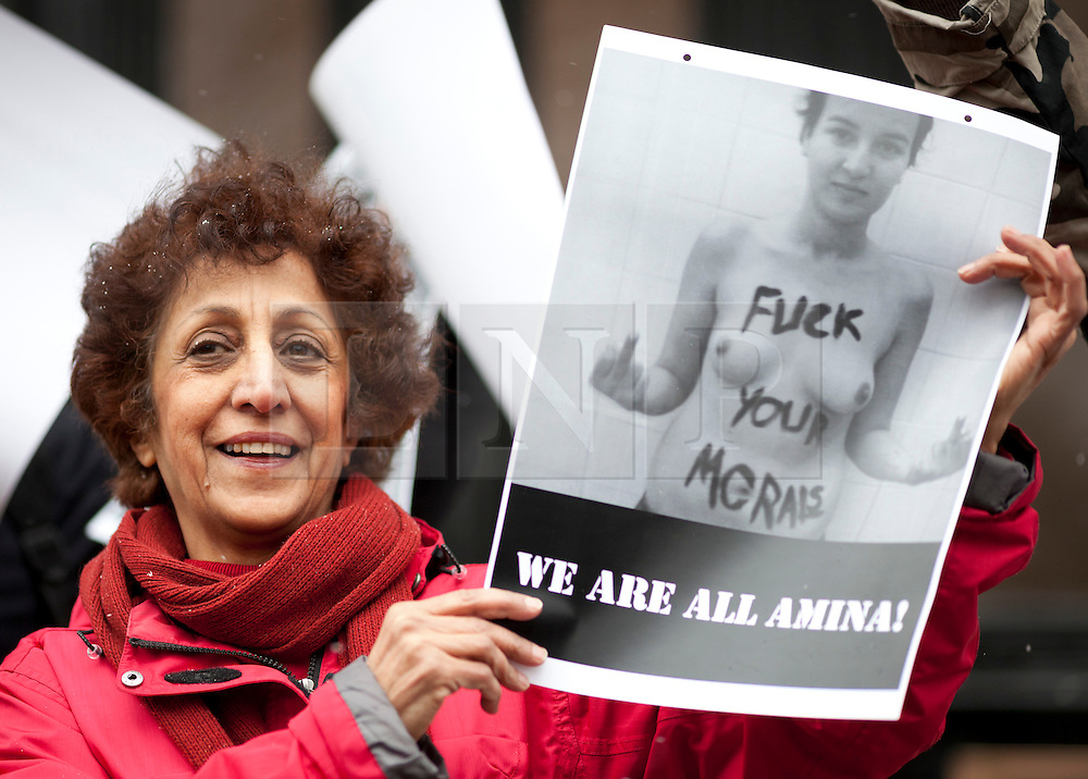 © Licensed to London News Pictures. 04/04/2013. London, UK. Femen protesters holding posters are seen demonstrating outside the Tunisian Embassy in London today (04/04/2013). Protests were organised across the world by Femen, an activist group, after they declared the 4th of April as ?topless jihad day? in a gesture of support for Amina Tyler, a Tunisian woman who was threatened with death by stoning for baring her breasts online. Photo credit: Matt Cetti-Roberts/LNP