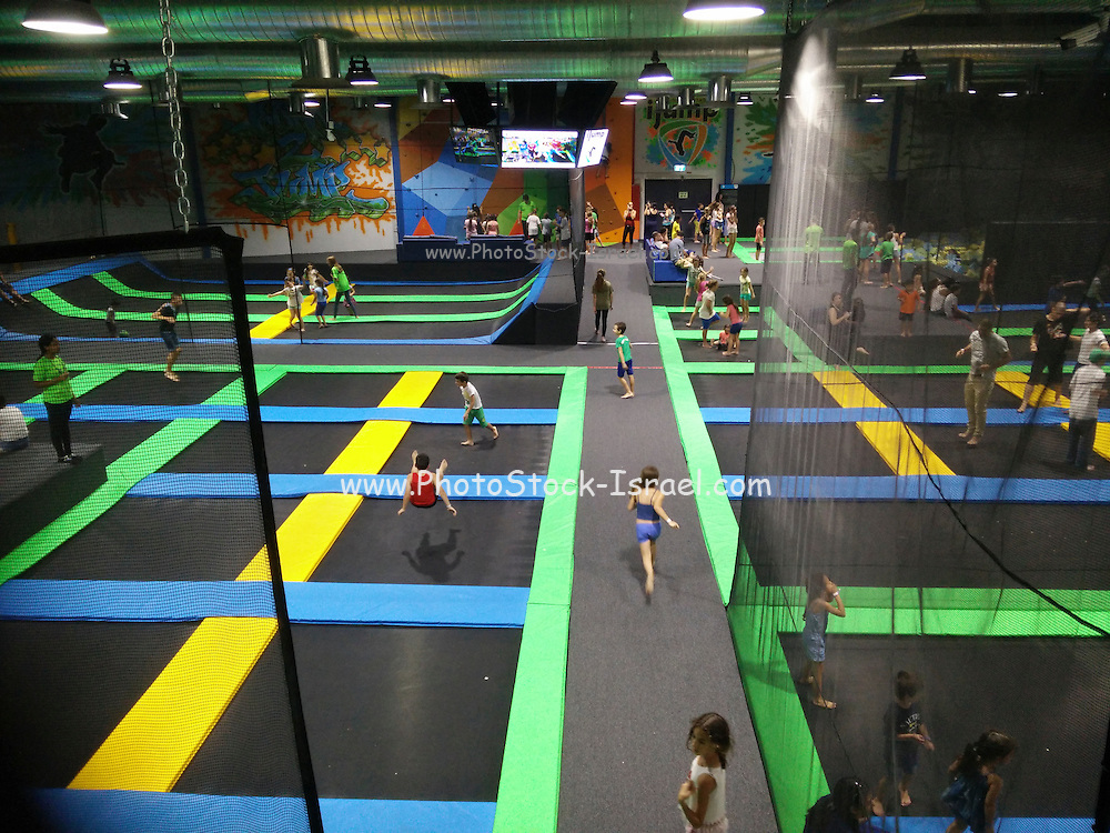 Children play on trampolines in a jump house