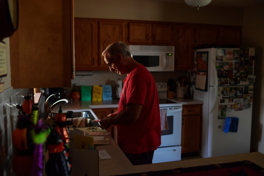 Jim Snoddy checks the mail in the kitchen of his home.