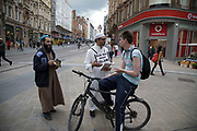 Muslim man wearing a sign which says  Ask me about Islam, stops people on the street to speak to them about his religious beliefs in central Birmingham, United Kingdom. In light of groups such as IS Muslims are keen to let people in the public, from other faiths that their religion is peaceful.