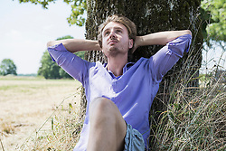 Mid adult man sitting under tree
