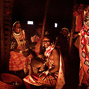Wilson's wedding day....Women gathered around the fire in Wilson's house. It is Wilson's wedding party and his village and home is full of visitors. The Maasais houses have very few and little windows with no glass and the only light is from a fire. The fire makes the room hot and smokey and is the focus point of much talk and laughter...It is mainly Maasais who live in the Loita Hills up above the Serengeti plains. They live in small villages and communities called bomas and live mainly of raising and selling live stock such as cattle and goats. Its a very remote region in Kenya, hard to get to without a four wheel drive with very little infrastructure and up till 2010 no mobile phone network. The Maasais are well known though out Kenya and the world for their colorful clothing and their way of keeping their old traditions alive.