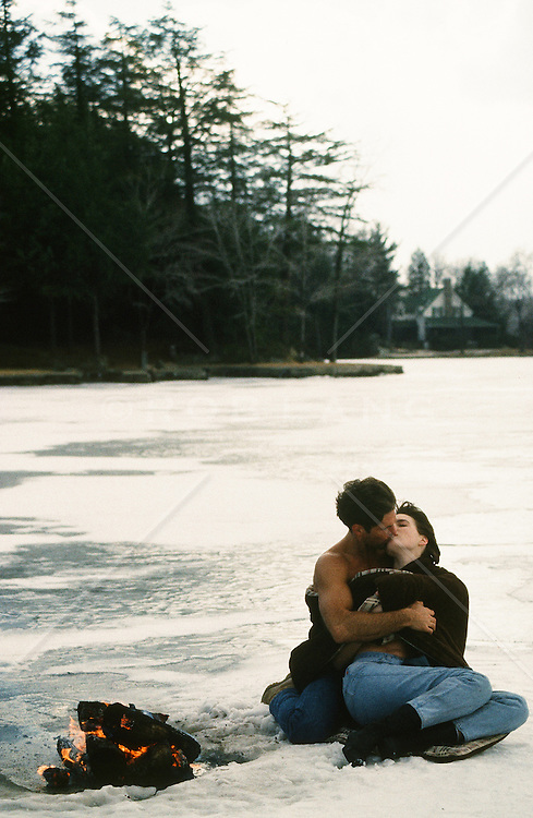 couple kissing while sitting on a frozen lake near a fire