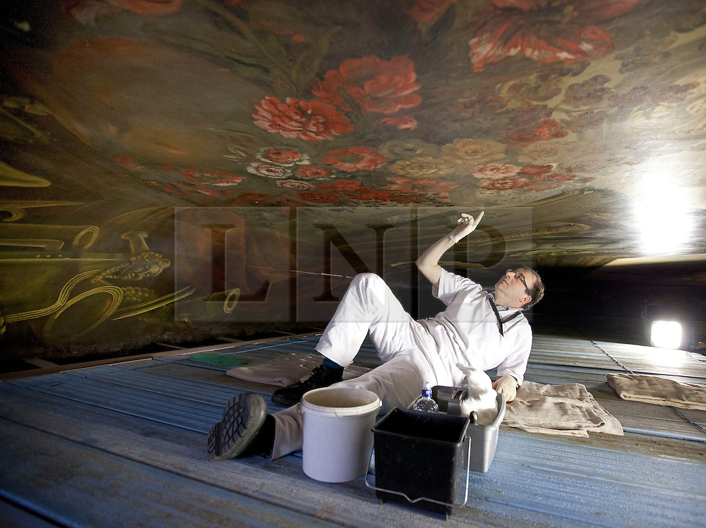 """© Licensed to London News Pictures. 04/03/2013. London, UK. On top of a scaffolding tower at around 40 feet in the air, restoration expert Francesco Rosellini examines damage to enamel during restoration work on the ceiling of the 'Painted Hall' at Greenwich Old Naval College in London today (04/03/2013). The conservation work, paid for by the Heritage Lottery Fund (HLF), is the 10th time the Painted Hall (often described as """"finest dining hall in Europe"""") will have been restored since its completion in 1784 and will have taken around five months to complete when the hall is unveiled to the public in May of this year. Photo credit: Matt Cetti-Roberts/LNP"""