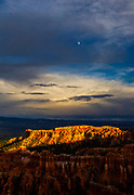 The moon rises in a break in storm clouds passing over the dramatic red rocks of Bryce Canyon National Park in Utah.
