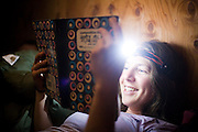 Meaghan Daly reads the hut journal at the backcountry North Pole Hut, San Juan Mountains, Colorado.
