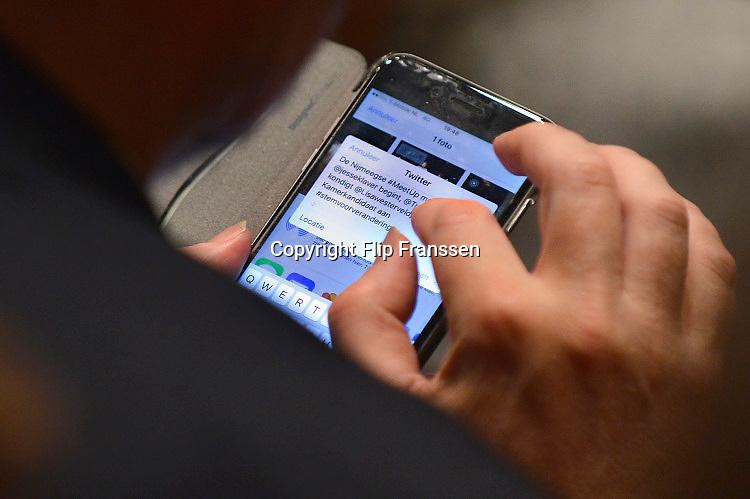 Nederland, Nijmegen, 13-1-2017 Een bezoeker zit met zijn mobiel, smartphone, op Twitter in een volle Vereeniging tijdens de verkiezings meetup van GroenLinks.Foto: Flip Franssen