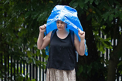 © Licensed to London News Pictures. 27/07/2021. London, UK. A woman uses a plastic bag to shelter from rain in Greenwich Park in South East London. A yellow weather warning for thunderstorms is in place for parts of England. Photo credit: George Cracknell Wright/LNP