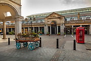 A shopping and entertainment hub in Londons West End, Covent Garden centres on the elegant, car-free Piazza, home to fashion stores, craft stalls and the Royal Opera House, empty during the coronavirus pandemic on the 10th May 2020 in London, United Kingdom. Covent Garden has experienced various stages of life. From humble beginnings as a Convent garden, it has moved through many guises over the centuries.  From a home to the aristocracy and the main centre of theatrical life in London it developed into the largest produce market in the world. The commercial vegetable market moved across the river to Nine Elms in 1974.