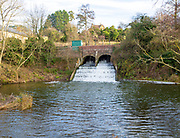 Bridge and weir with rushing water on River Marden, Bremhill, Calne, Wiltshire, England, UK