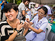 "15 JUNE 2014 - BANGKOK, THAILAND: A woman gets an immunization during a health and wellness screening at a ""Return Happiness to Thais"" party in Lumpini Park in Bangkok. The Thai military junta, formally called the National Council for Peace and Order (NCPO), is sponsoring a series of events throughout Thailand to restore ""Happiness to Thais."" The events feature live music, dancing girls, military and police choirs, health screenings and free food.   PHOTO BY JACK KURTZ"