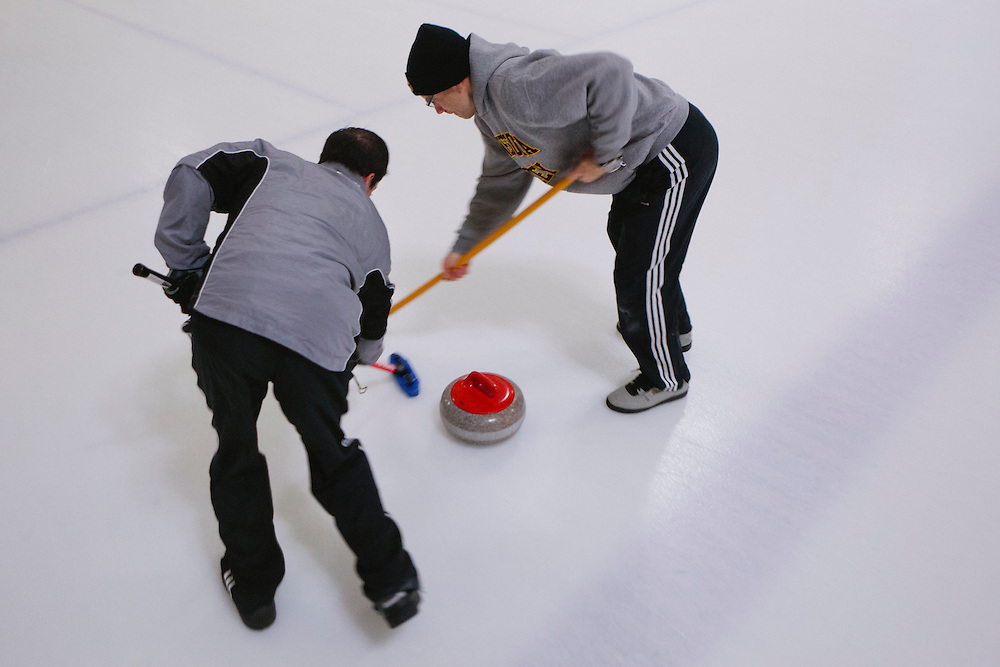 Ryan Winterbourne, left, and Brian Zaitz, both of San Jose, sweep during the San Francisco Bay Area Curling Club's Tuesday night league at Sharks Ice in San Jose on Jan.15, 2013.