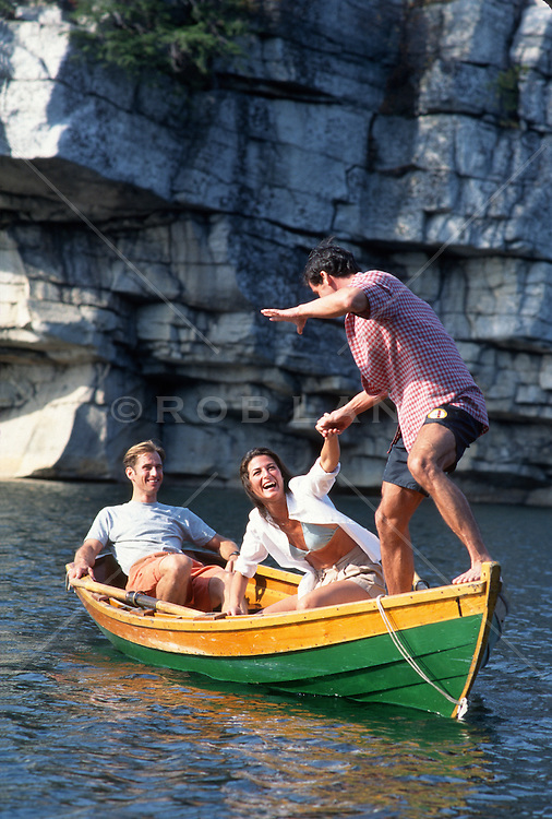 Couple in a boat watching a man in the same boat balance On the edge