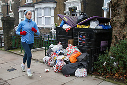 © Licensed to London News Pictures. 28/12/2020. London, UK. A runner jogs past bags of rubbish gathered in a front garden in north London after the festive period. Photo credit: Dinendra Haria/LNP