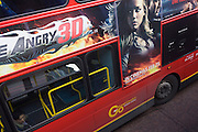 A 3D movie poster for Drive Angry on the side of a red London double-decker bus with a lone passenger on the lower deck.