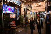 New York, NY - 3 November 2020. New York City anticipates presidential election results as polls in some states close. The Liberty, on West 35th Street, has a TV on the sidewalk so passers-by and outdoor diners can follow the election results.
