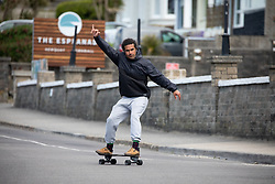 "© Licensed to London News Pictures. 11/05/2020. Newquay, UK. A man skateboards near Fistral beach on the North coast of Cornwall, the day after British Prime Minister Boris Johnson announced a 'road map' to lift lockdown restrictions due to Covid-19, (Coronavirus). A rise in ""staycations"" - the concept of holidaying in your home country rather than travelling abroad - is expected, with many visitors planning to visit Cornwall. However, an ongoing campaign titled ""#ComeBackLater"" is trying to persuade tourists not to visit the county until it is safe to do so. Photo credit : Tom Nicholson/LNP"