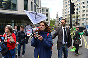Climate change activist from the Extinction Rebellion group march and sing songs close to St Pauls tube station demanding that the British Government acknowledge the climate crisis posed by global warming on 25th April 2019 in London, England, United Kingdom.