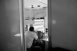 macchinista del treno nella sua cabina attende il segnale di partenza. Reportage che analizza le situazioni che si incontrano durante un viaggio lungo le linee ferroviarie delle Ferrovie Sud Est nel Salento