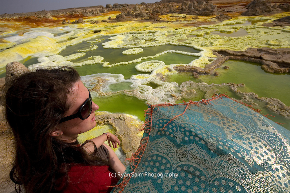 Lauren Bobowski takes refuge from the scorching sun under an umbrella at sulfer pools in Dallol