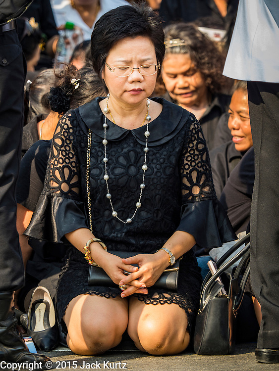 16 DECEMBER 2015 - BANGKOK, THAILAND:  A woman prays during the funeral for Somdet Phra Nyanasamvara, Thailand's Supreme Patriarch, during the Patriarch's funeral. He died Oct. 24, 2013. He was ordained as a Buddhist monk in 1933 and appointed as the Supreme Patriarch in 1989. He was the spiritual advisor to Bhumibol Adulyadej, the King of Thailand when the King served as a monk in 1956. Tens of thousands of people lined the streets during the procession to pray for the Patriarch.    PHOTO BY JACK KURTZ
