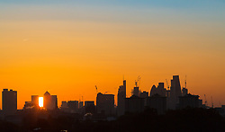 London, October 27 2017. The sun emerges from behind the skyscrapers of Docklands as the day breaks over London, seen from Primrose Hill. © Paul Davey