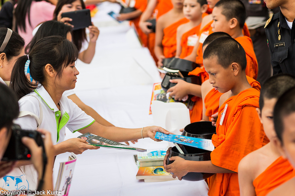 """23 APRIL 2013 - BANGKOK, THAILAND:   Thais place books donated to Thai literacy projects into monks' alms bowls during the opening ceremony to mark Bangkok as the World Book Capital City 2013. UNESCO awarded Bangkok the title. Bangkok is the 13th city to assume the title of """"World Book Capital"""", taking over from Yerevan, Armenia. Bangkok Governor Suhumbhand Paribatra announced plans that the Bangkok Metropolitan Administration (BMA) intends to encourage reading among Thais. The BMA runs 37 public libraries in the city and has modernised 14 of them. It plans to build 10 more public libraries every year. Port Harcourt, Nigeria will be the next World Book Capital in 2014..PHOTO BY JACK KURTZ"""