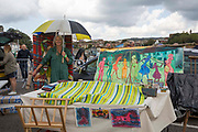 An artist protects her work with a blanket and umbrella from the rain during the 2017 Art Car Boot Fair, Folkestone, Kent.