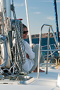 A woman (MR available) relaxes against the mast on the deck of a sailboat in the Sea of Cortez