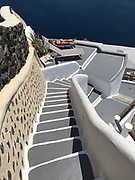 Classic view of staircase with woman sunbathing on deck, Oia, Santorini, Greece.