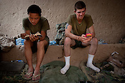 Marines relax on a hot afternoon at Patrol Base McElhinney, reading an playing GameBoy.